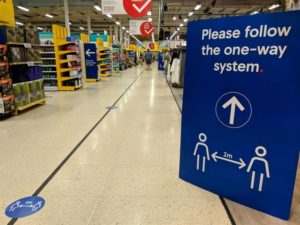 Image of inside a supermarket with a blue sign saying please follow the one-way system and floor markings
