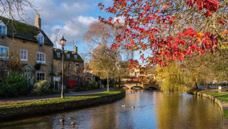 Pretty village shot from Gloucestershire with river next to cottages and trees