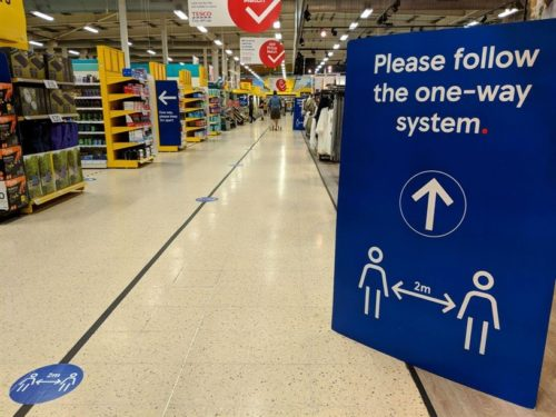 Image of inside a supermarket with a social distancing sign saying please follow the one-way system and floor markings