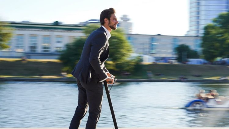 Image showing man on e-scooter next to a river