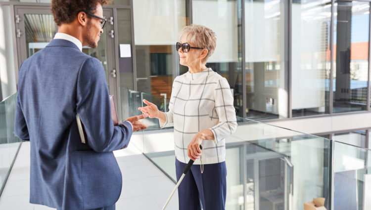 two business people in conversation, a woman who is a cane user and a man in a suit.