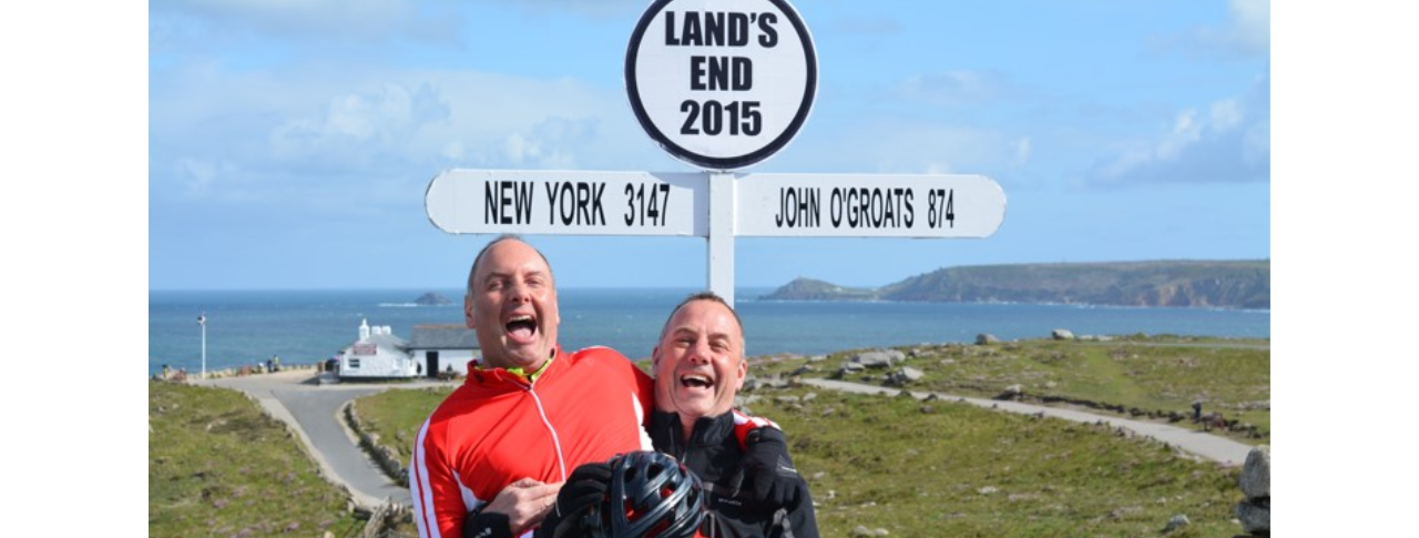 Steve and brother laughing, one carrying the other, they are standing in front of a sign that reads Land's end 2015