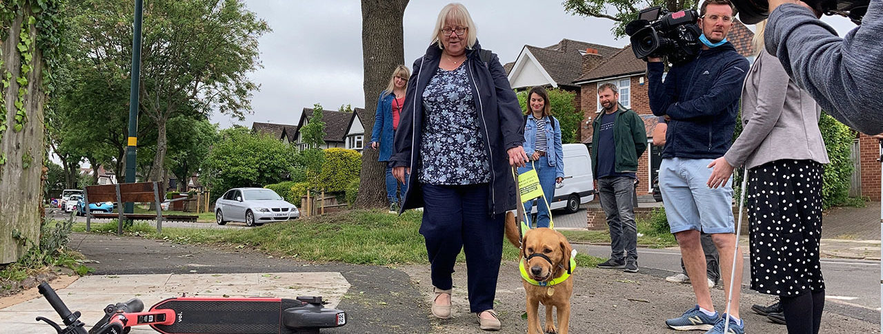 a guide dog user walks by a badly parked e-scooter, other people are standing by and watching.