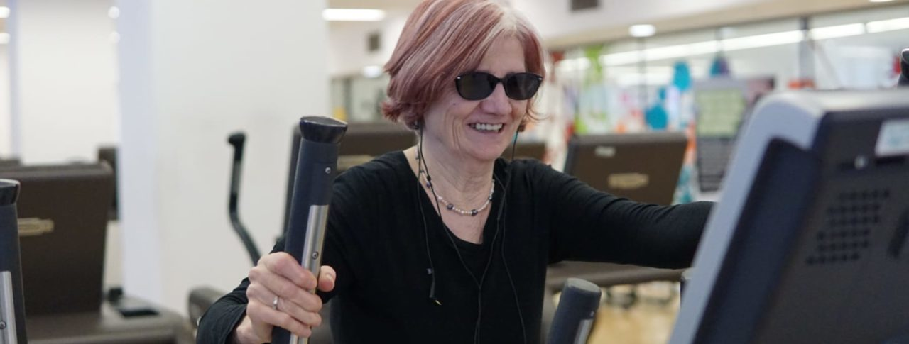 Image of blind person enjoying exercise on a treadmill in a gym