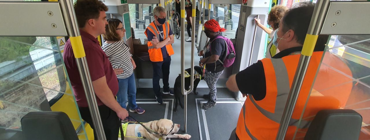 A group of people inside a train, some are guide dog users, some are wearing high-vis vests.