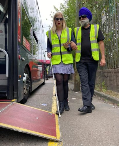 Two people wearing Hi-vis jackets. A cane user is guiding a man wearing sim-specs get onto a bus.