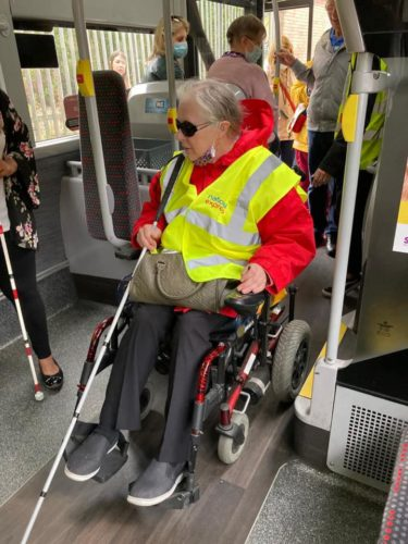 a wheel chair and white cane user aboard a bus