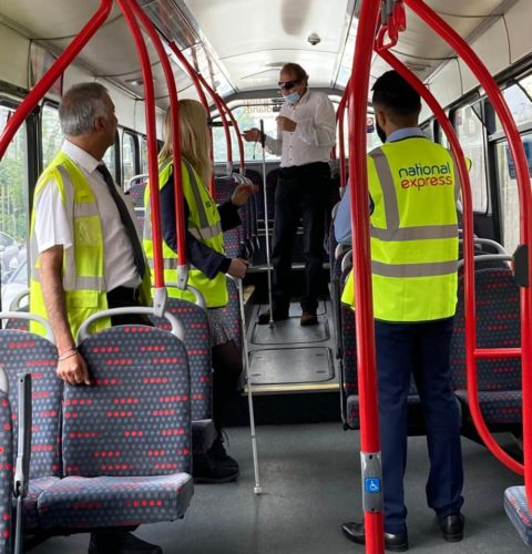 A group of people wearing hi-vis jackets are aboard a bus, some of whom are white cane users.