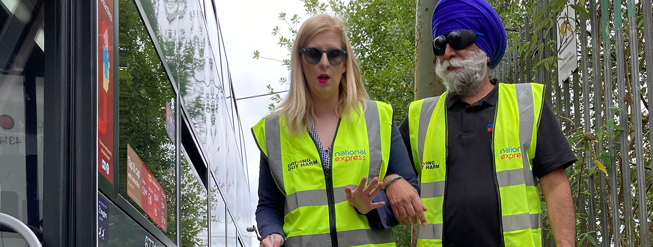A woman with a white cane guiding a man wearing sim specs by a bus, both wearing high vis vests