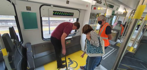 Two people examine the electric sockets in the wheelchair area of a train carriage, a man in a high-vis vest is standing by