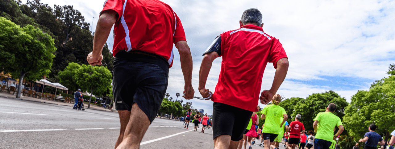 blind runner and his companion joined by a cord to guide him during an amateur competition surrounded by other runners reaching the finish line.